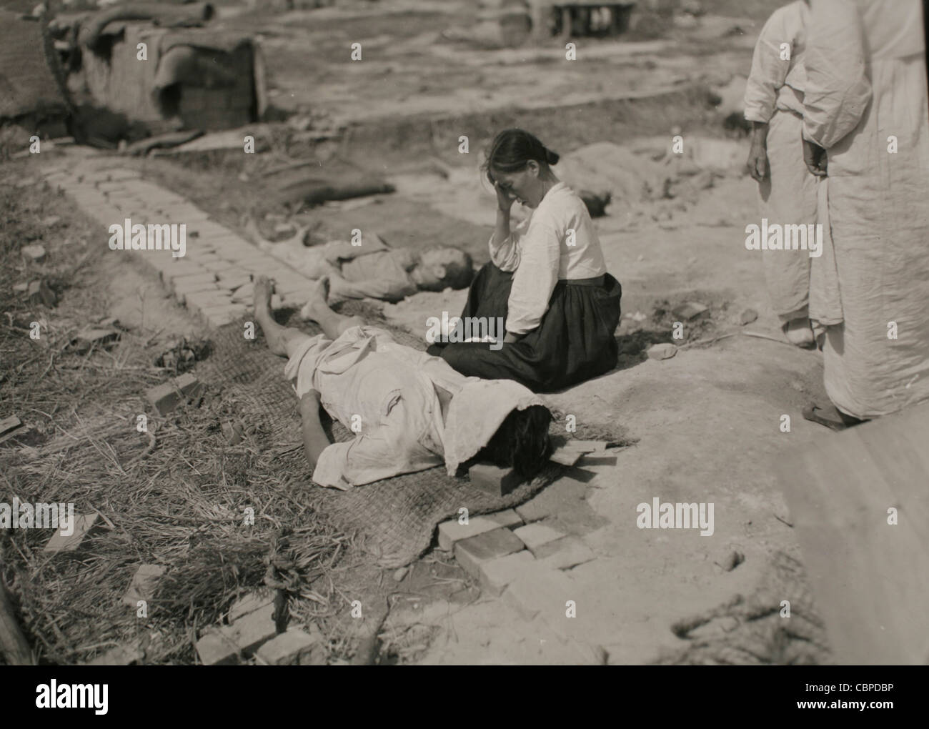 Korea, 29 September 1950: Korean woman weeps beside the body of her husband who was slain by the North Korean troops - Stock Image