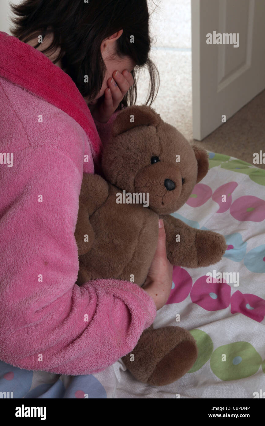 Over the shoulder irl clutching a teddy bear sitting on her bed hand over her eyes crying. - Stock Image