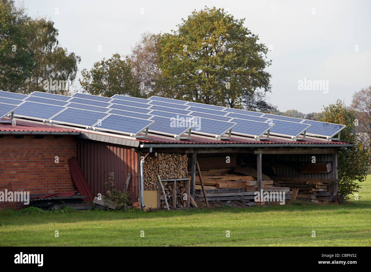 Solar energy panels fitted to farm buildings, Strohen, Lower Saxony, Germany. - Stock Image