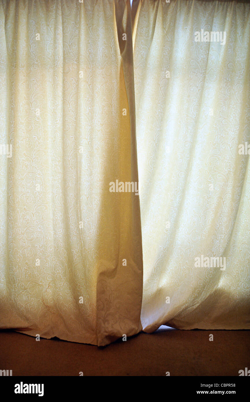 Curtains pulled across large window - Stock Image