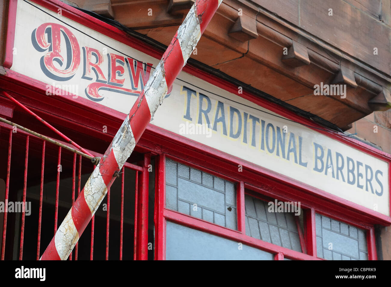Red and white stripped pole of a traditional barbers shop. - Stock Image