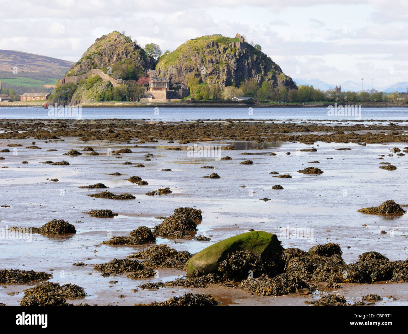 Dumbarton Rock with castle, River Clyde, and the tide is out. - Stock Image