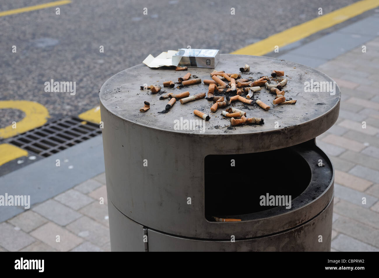 Street refuse bin with stubbed out cigarette ends. - Stock Image