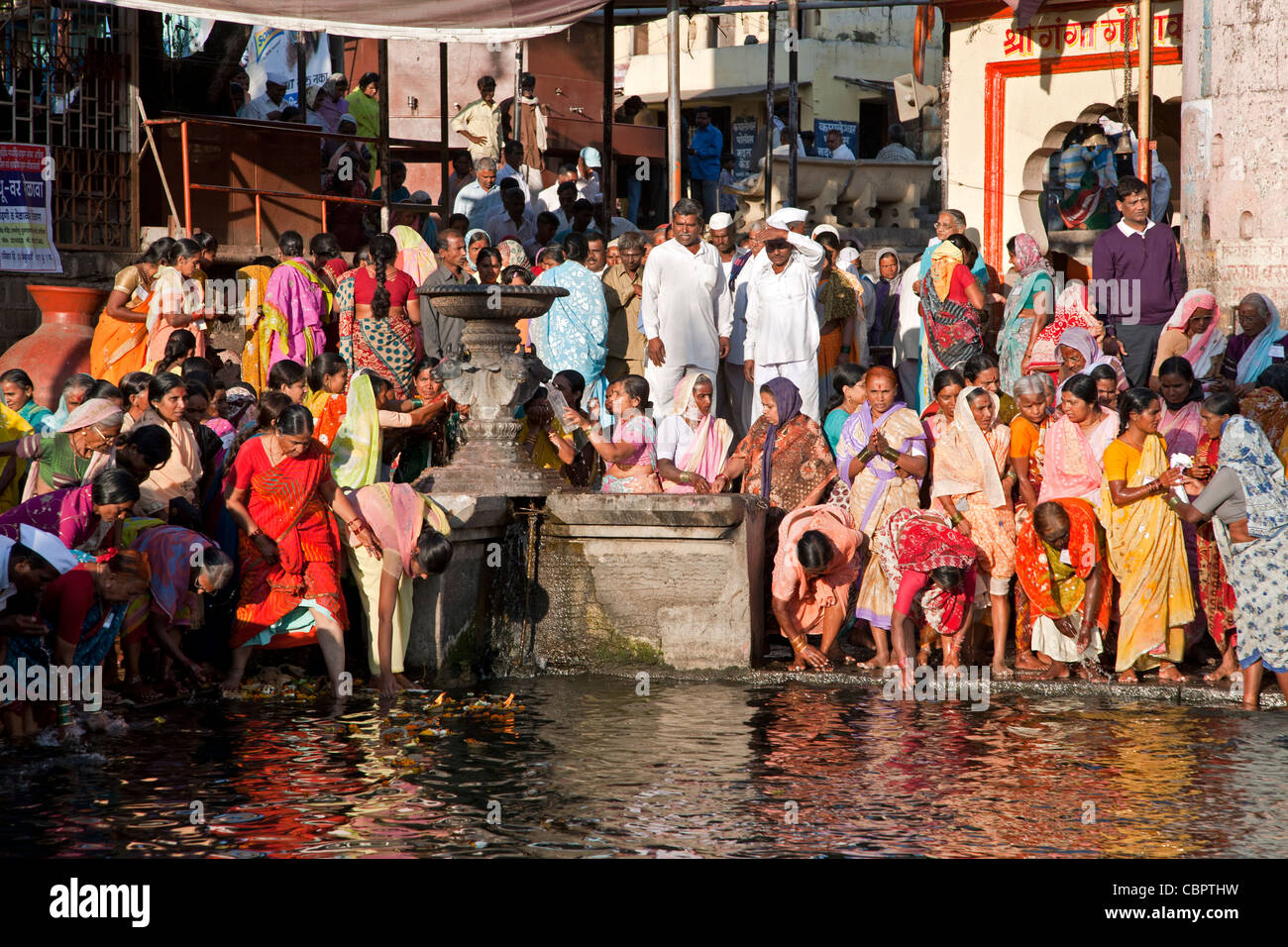 Women taking the ritual bath in the sacred waters of the Godavari river. Ram Kund. Nasik. India Stock Photo
