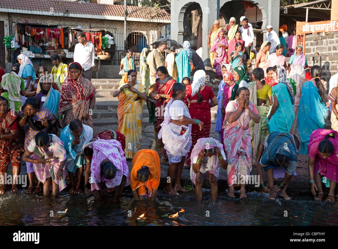 Women taking the ritual bath in the sacred waters of the Godavari river. Ram Kund. Nasik. India Stock Photo