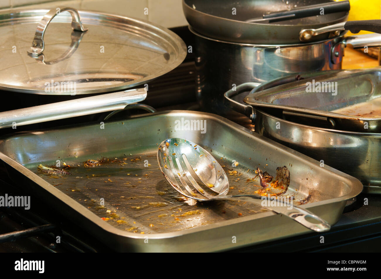 A selection of roasting tins, saucepans and frying pans in a kitchen waiting to be washed up. - Stock Image