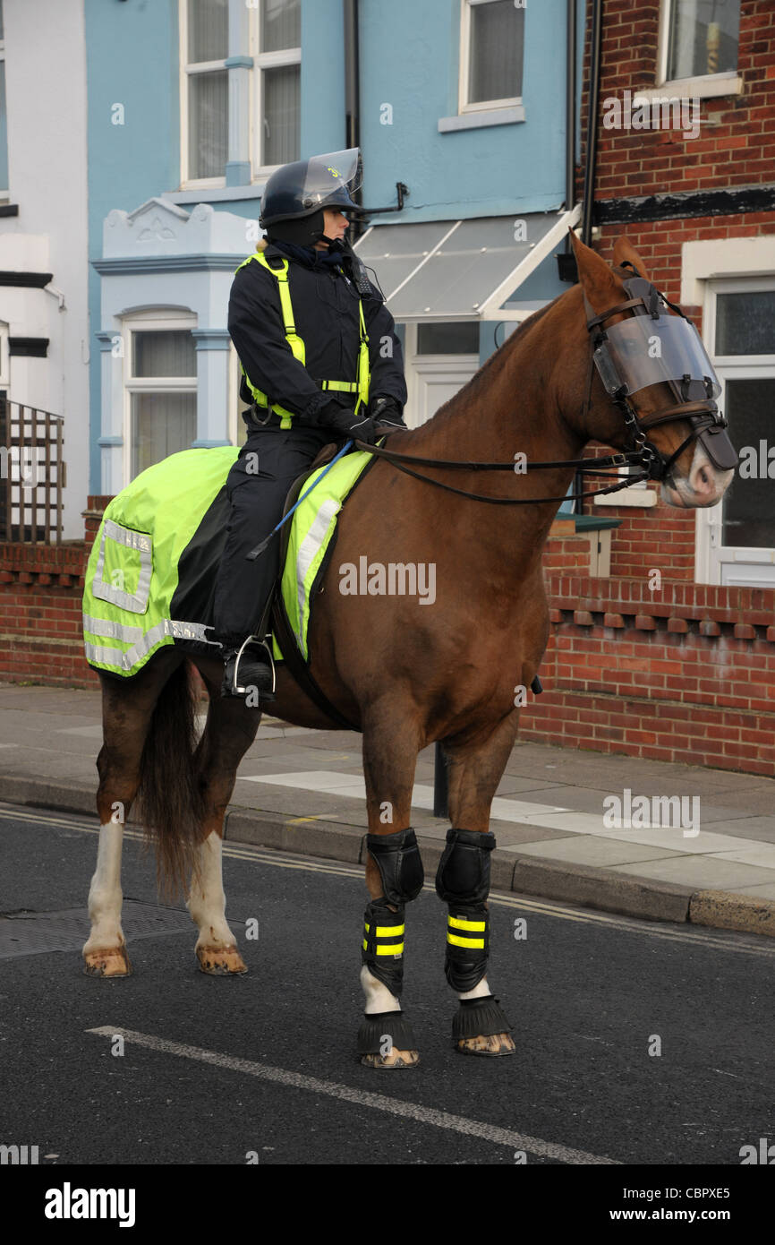 A mounted police officer and horse in protective riot dress during a football match crowd control. Portsmouth Hampshire. Stock Photo