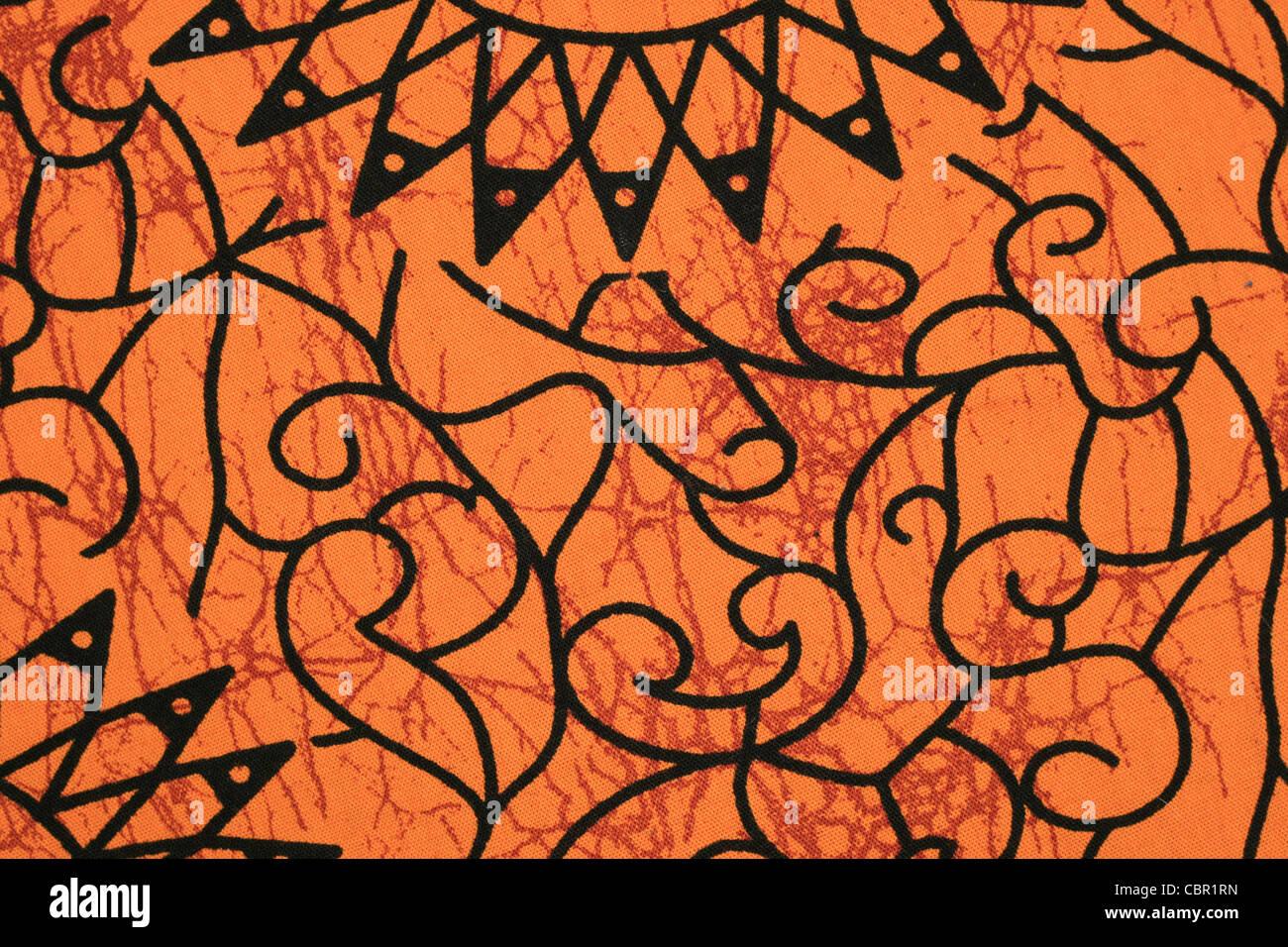 orange and black Tanzanian cloth pattern detail - Stock Image
