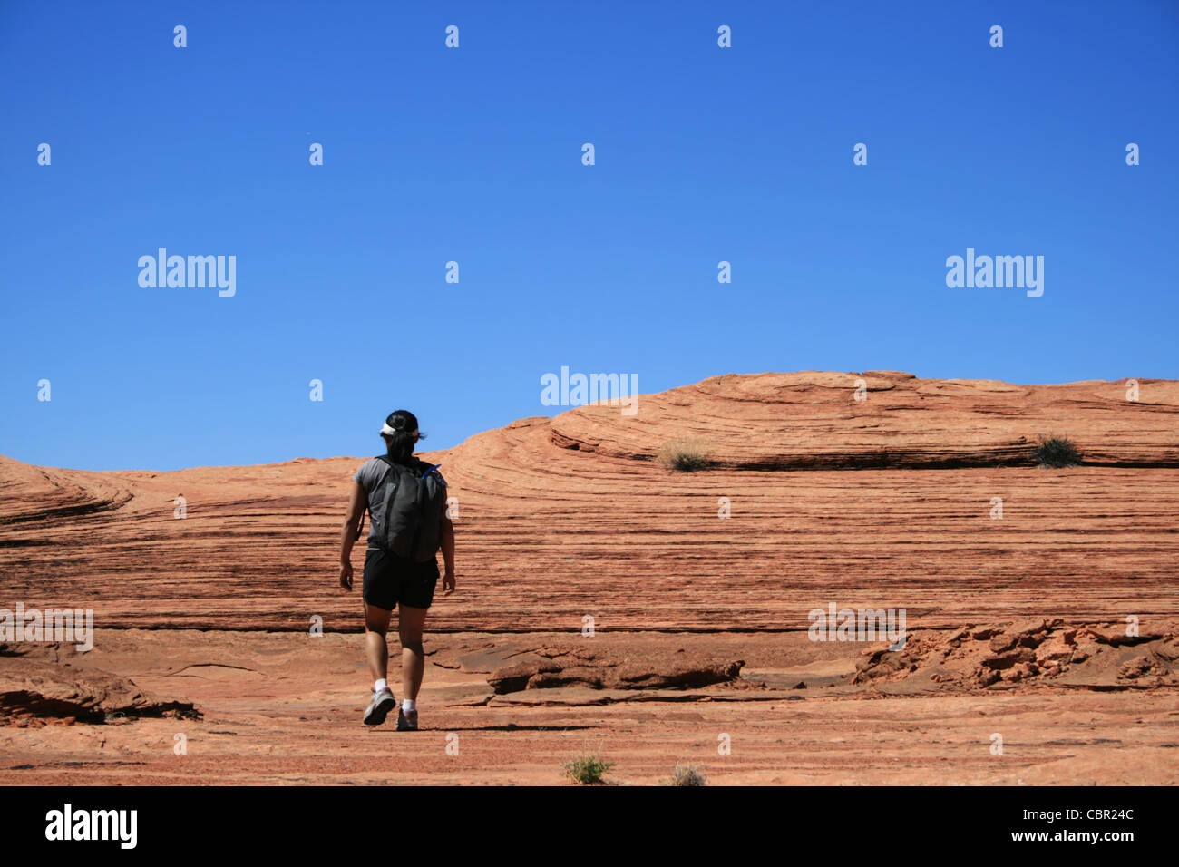 a woman walks across sandstone slickrock in the desert with blue sky copy space - Stock Image