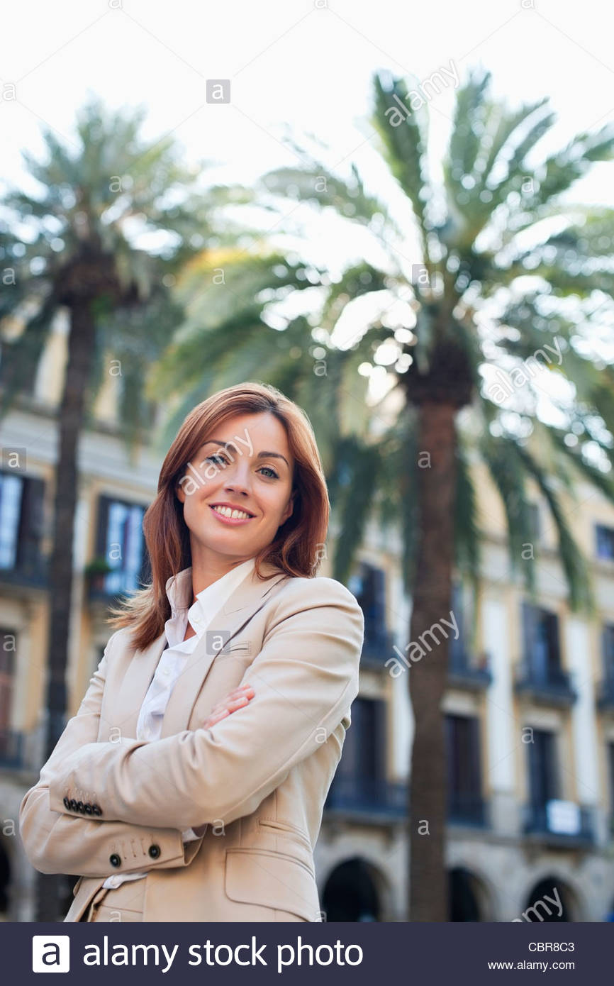 Businesswoman outdoors with arms crossed - Stock Image