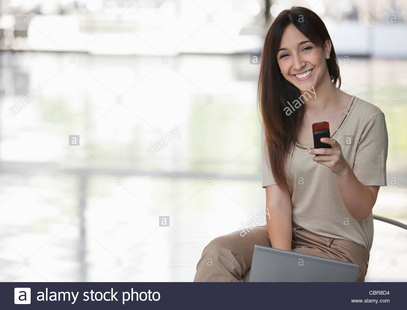 Businesswoman text messaging on cell phone in lobby - Stock Image