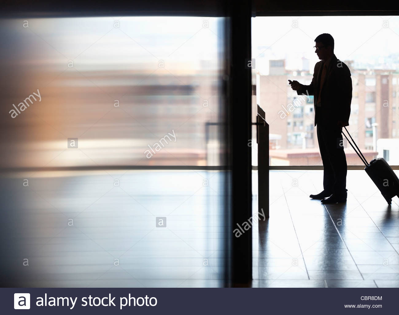 Businessman pulling luggage and using cell phone - Stock Image