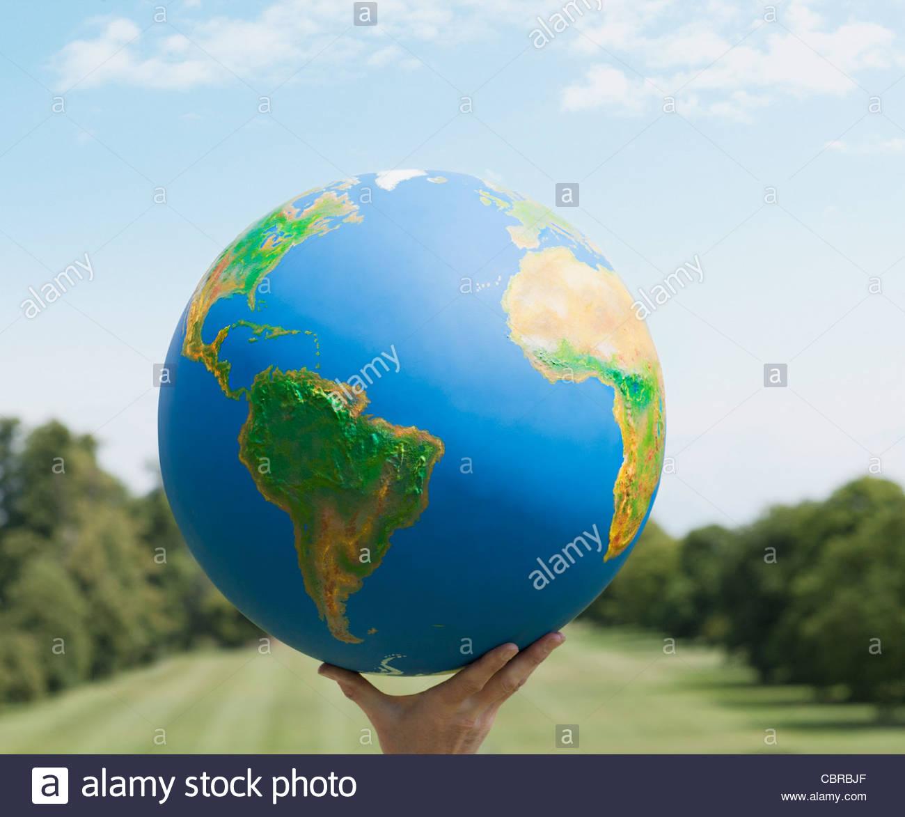 Hand holding large globe outdoors - Stock Image