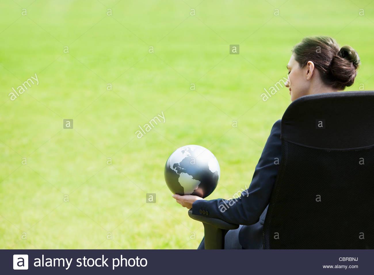 Businesswoman sitting outdoors holding globe - Stock Image