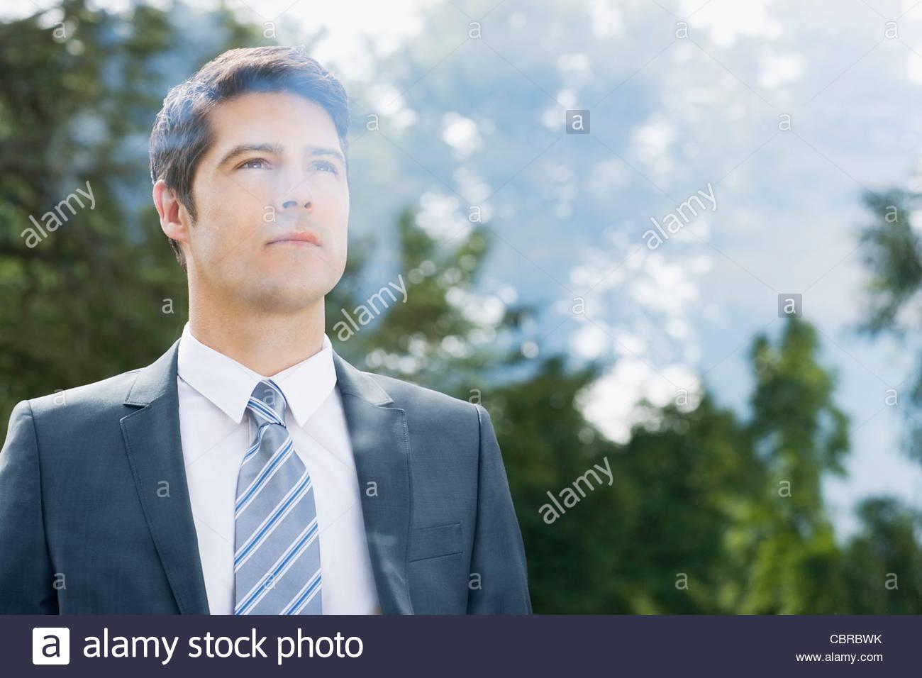 Businessman looking through window - Stock Image