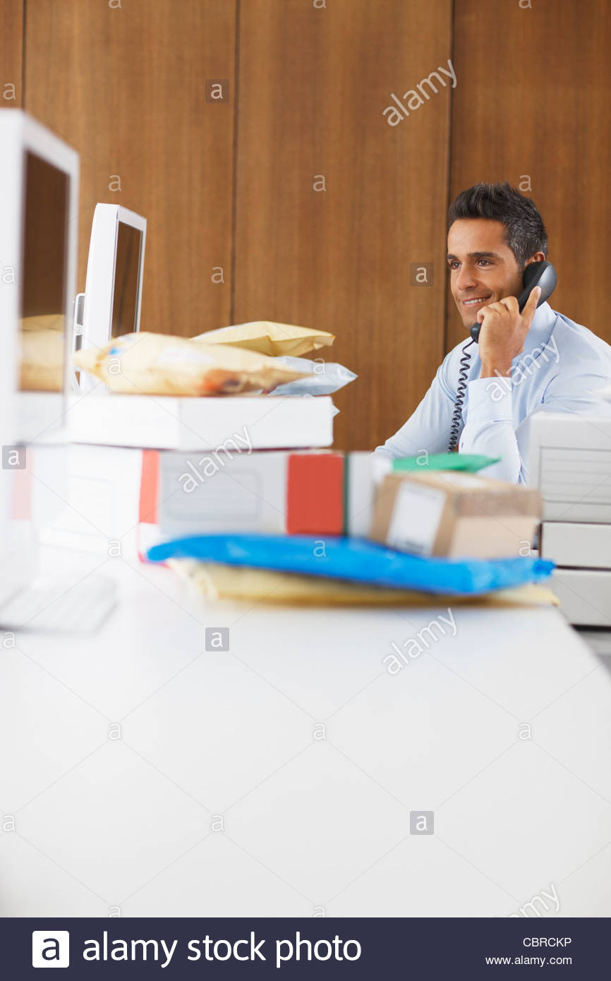 Businessman sitting at desk covered in packages - Stock Image