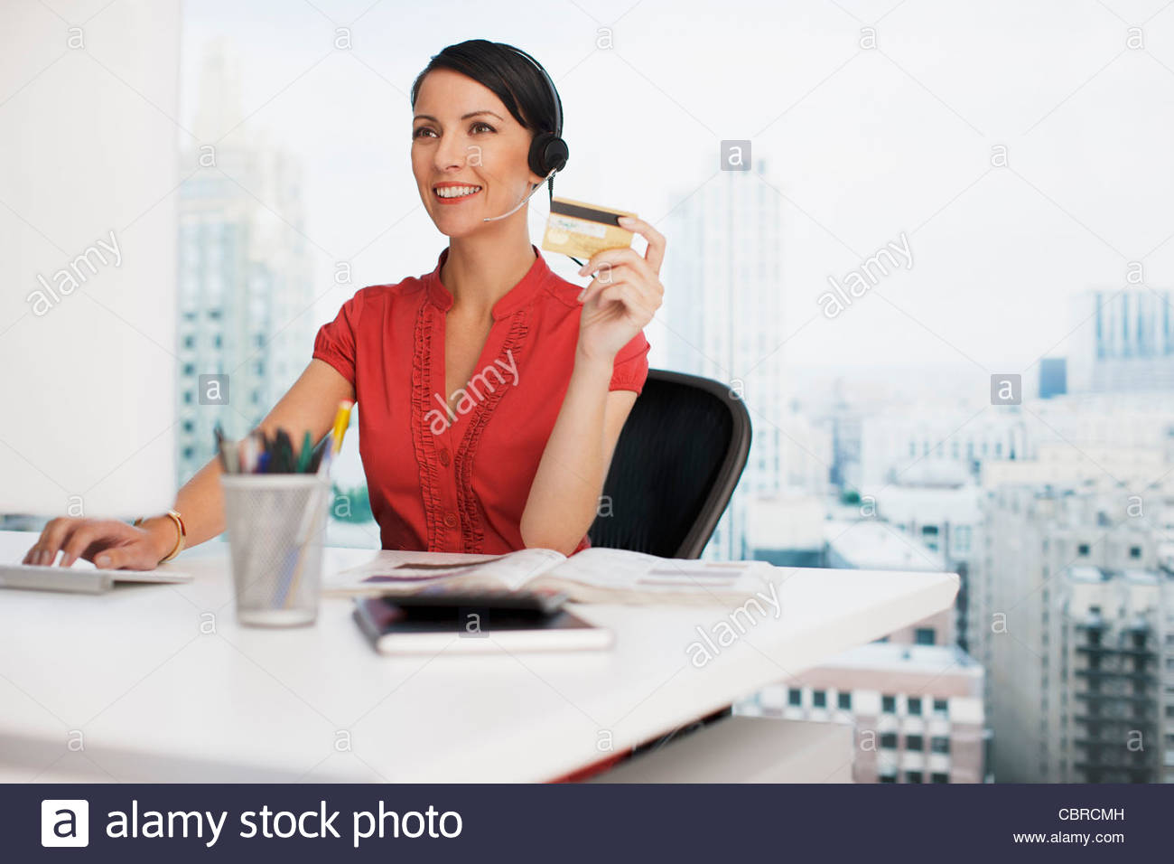 Businesswoman holding credit card at office desk - Stock Image
