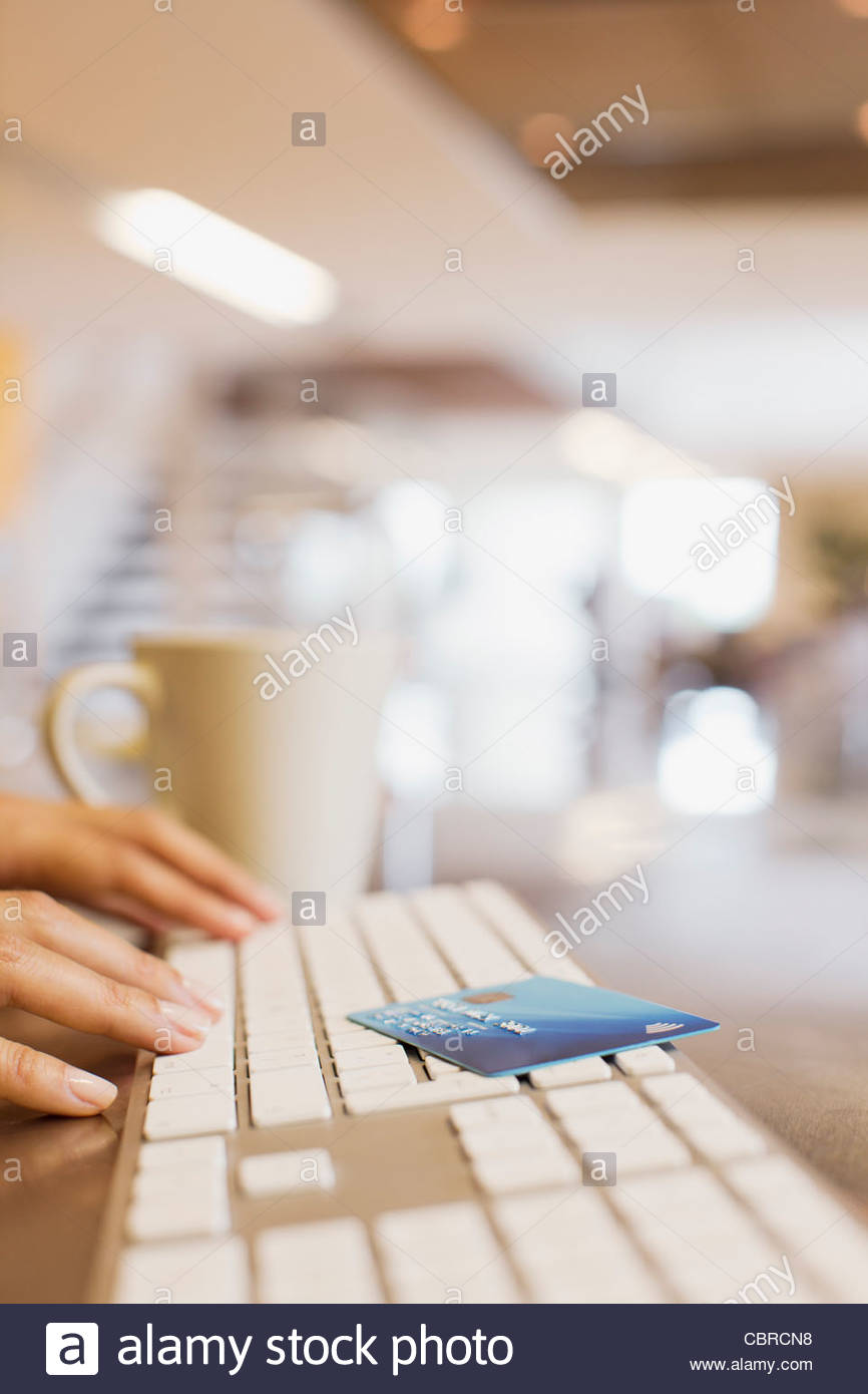 Close up of woman credit card and woman typing on keyboard - Stock Image