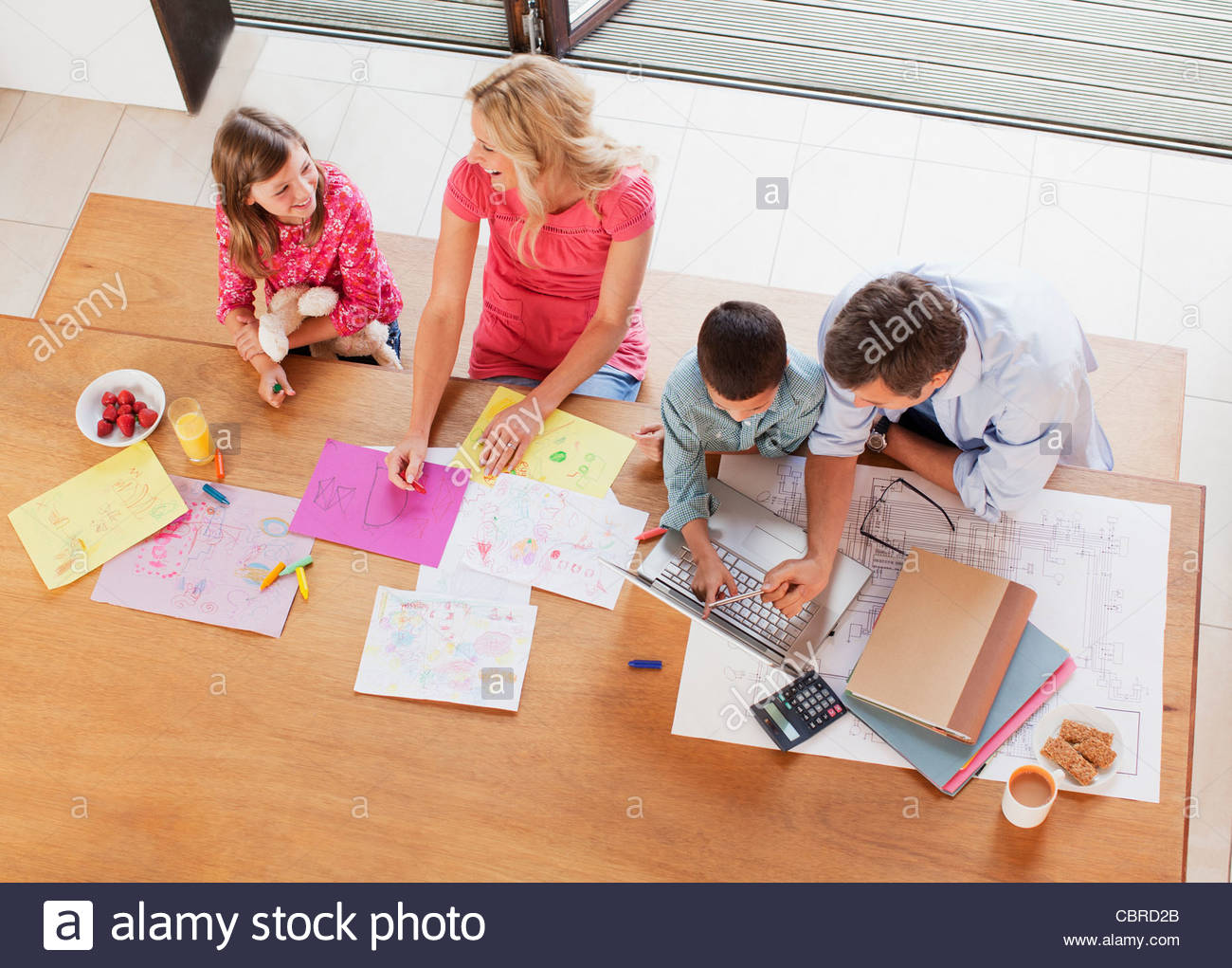 Family relaxing together at table - Stock Image