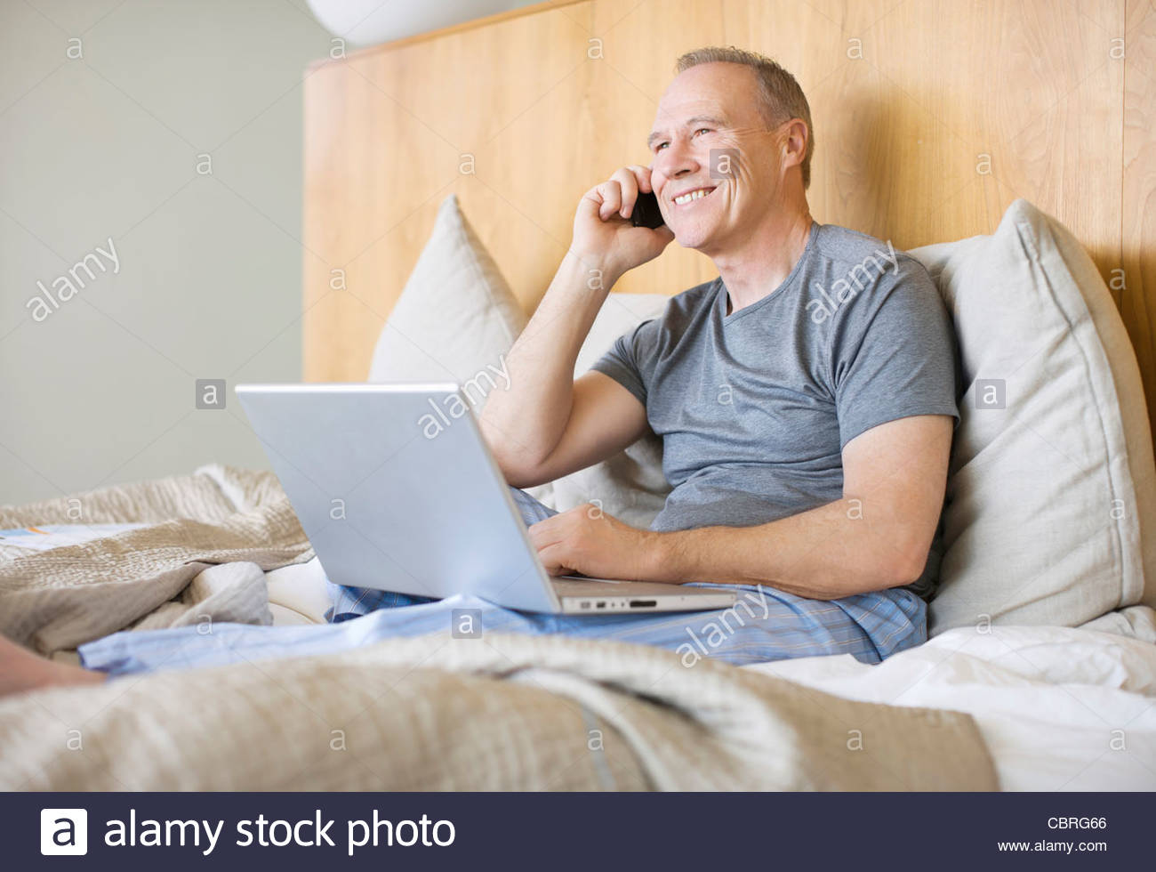 Man sitting in bed using laptop and cell phone - Stock Image