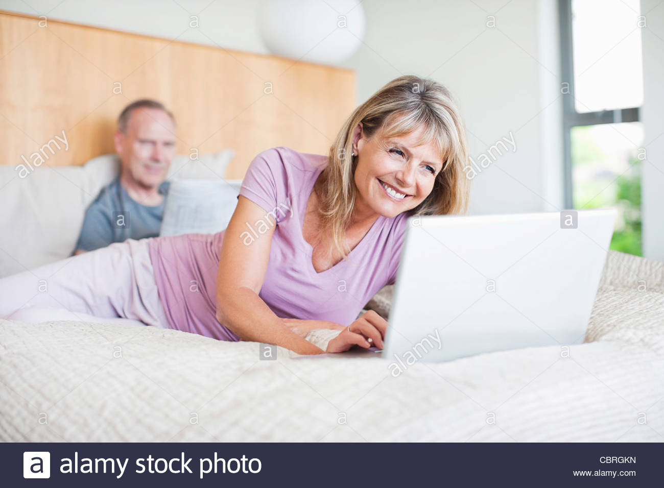 Woman laying on bed using laptop - Stock Image