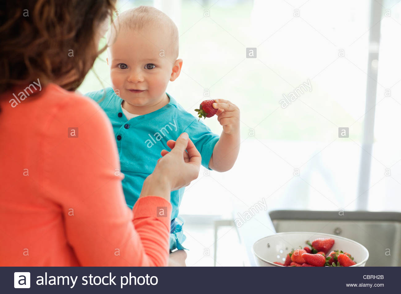 Mother giving baby strawberry - Stock Image
