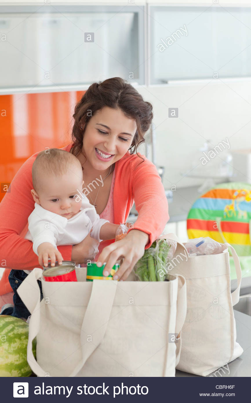 Woman holding baby and unloading groceries from reusable bag - Stock Image
