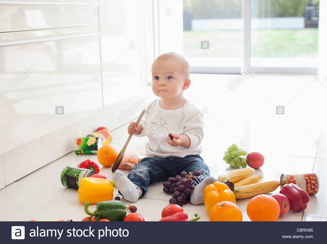 Baby making mess on floor with food - Stock Image