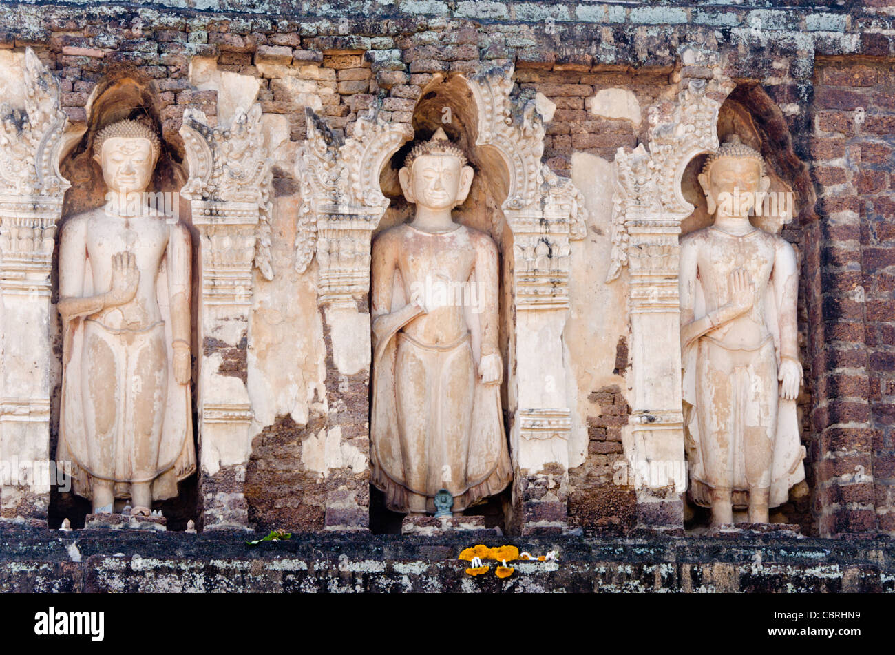 Midsection of the 900 year old chedi (stupa) with standing Buddhas at Wat Chama Thewi in Lamphun in Thailand with - Stock Image
