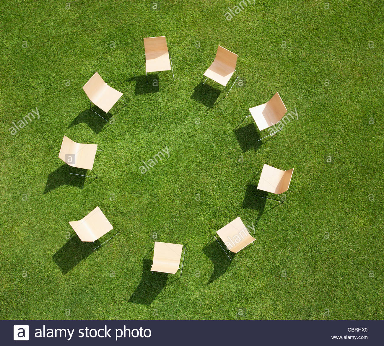 Chairs in circle formation on grass - Stock Image