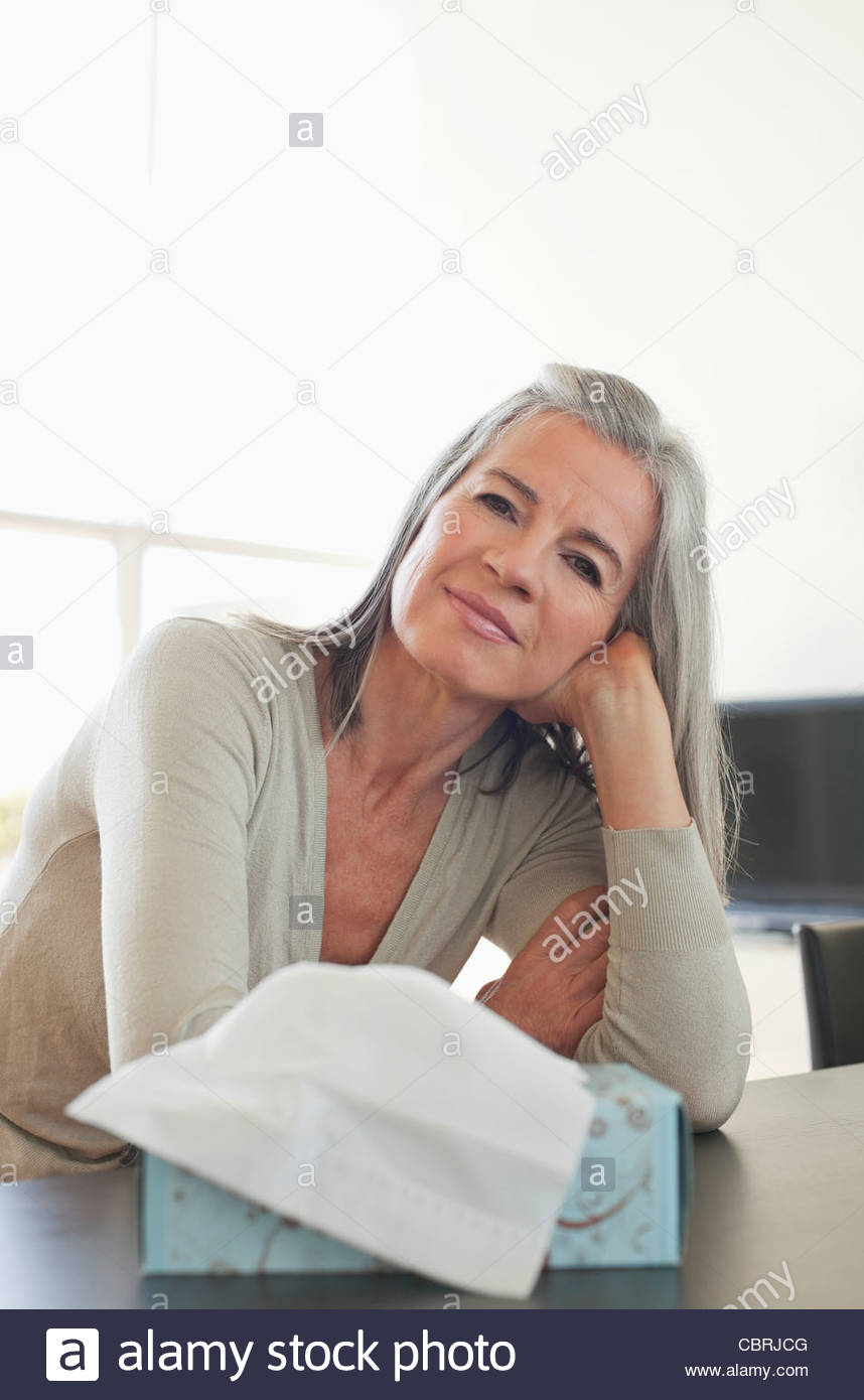 Woman leaning on hand with tissue in foreground, - Stock Image