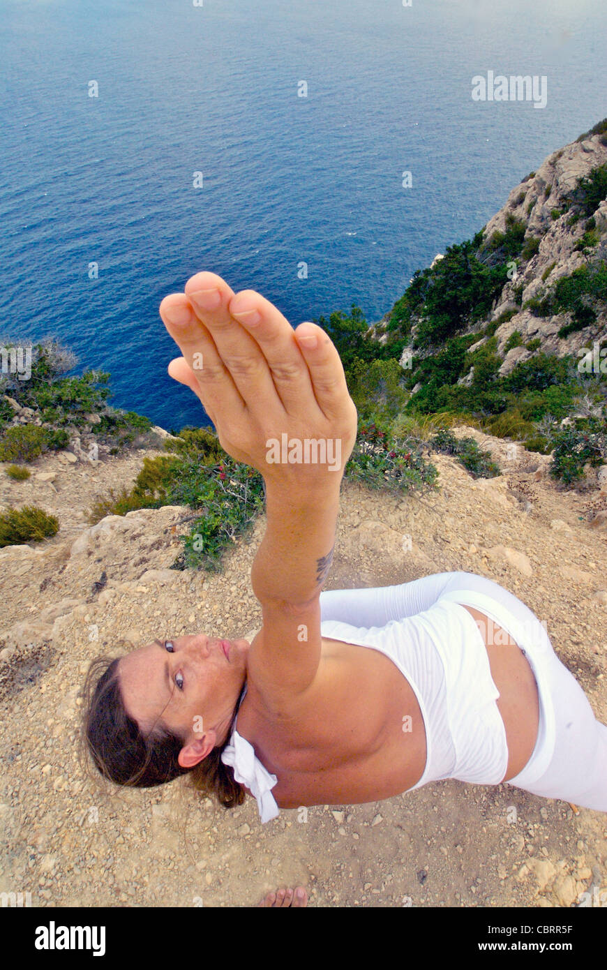 Model Released: Attractive young woman, artist Lena Tancredi, practicing yoga in front of the Mediterranean Sea, - Stock Image