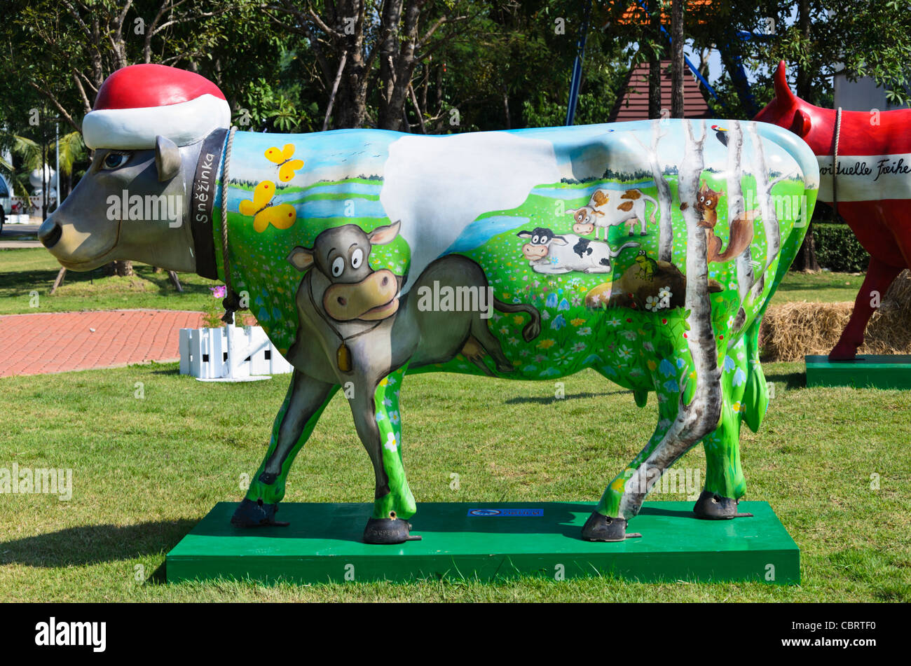 Fanciful cow statue painted with scene of other cows grazing and a Santa hat at Dutch exhibit at expo in Chiang - Stock Image