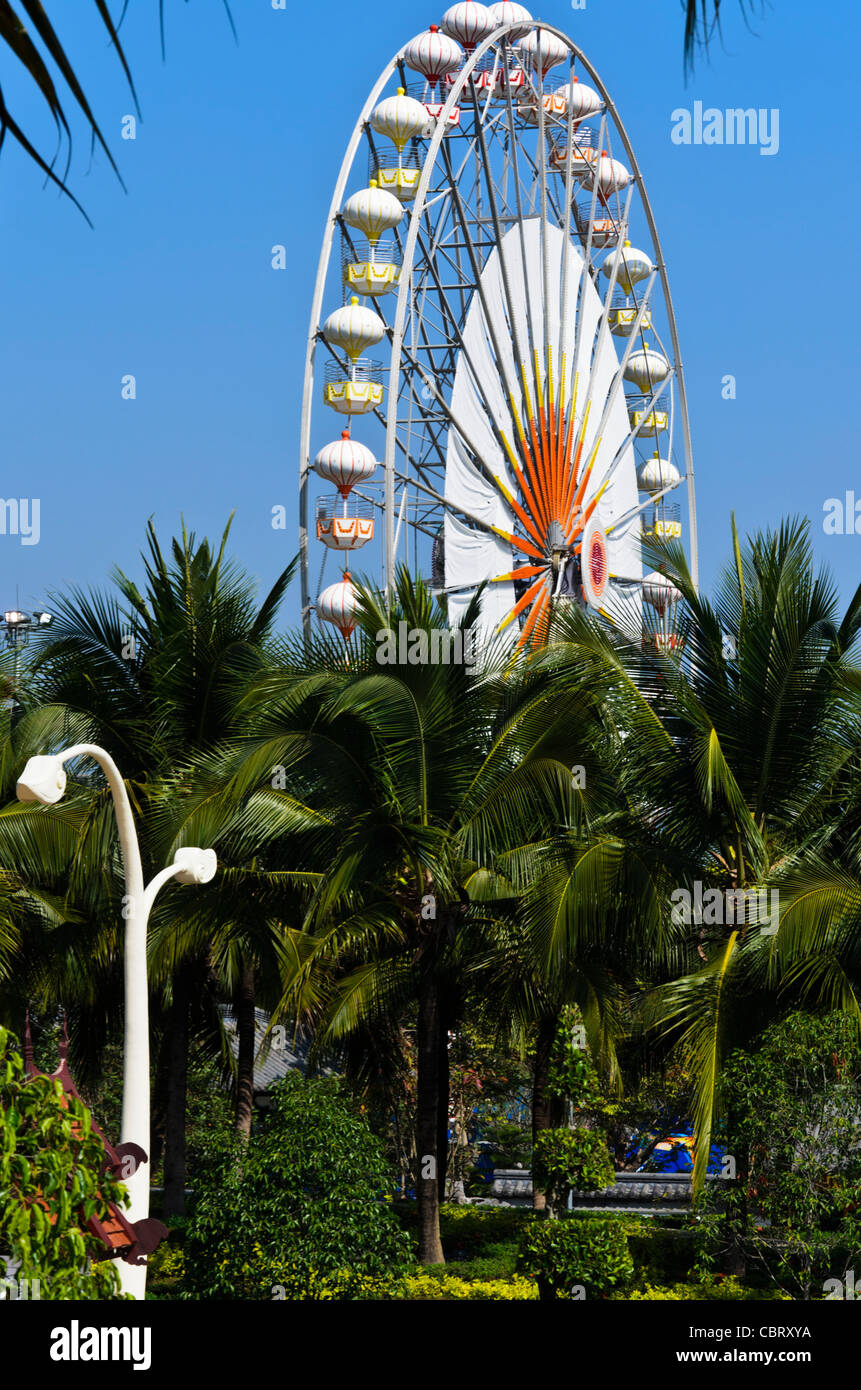 Enormous Ferris wheel above palm trees at Royal Flora Ratchaphruek in Chiang Mai Thailand with artsy sculptured - Stock Image