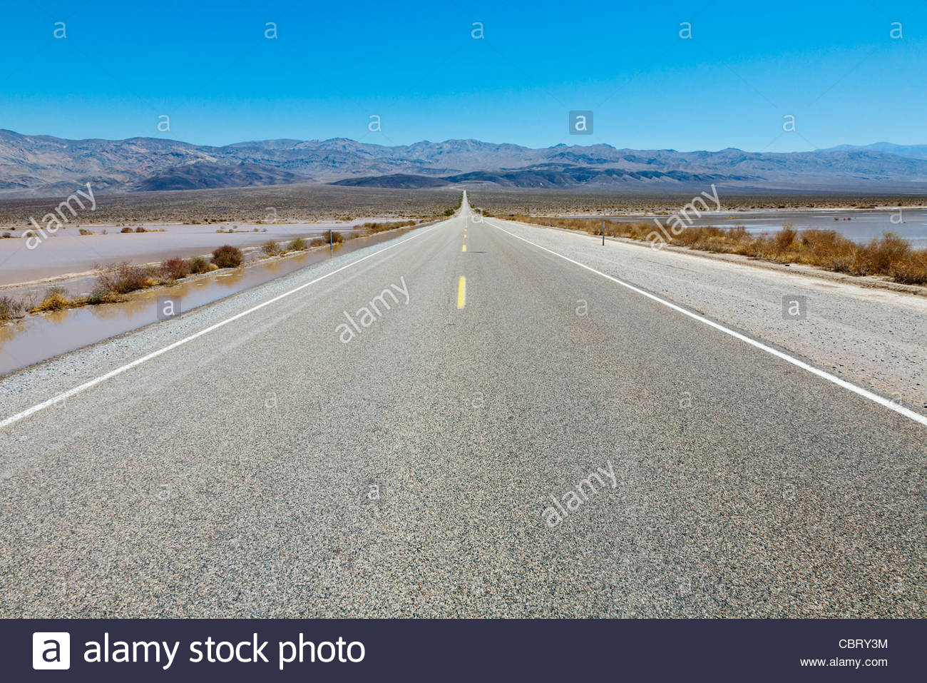 Empty desert Road stretching into the distance, Death Valley National Park, California, United States - Stock Image