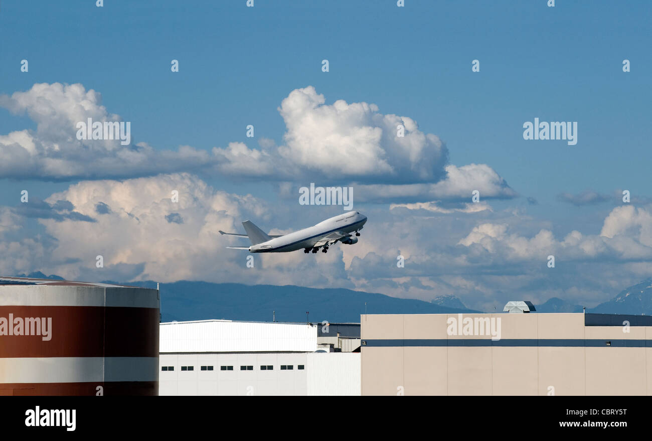 Taking-off white (no name no logo) Jumbo 747 above airport buildings - Stock Image