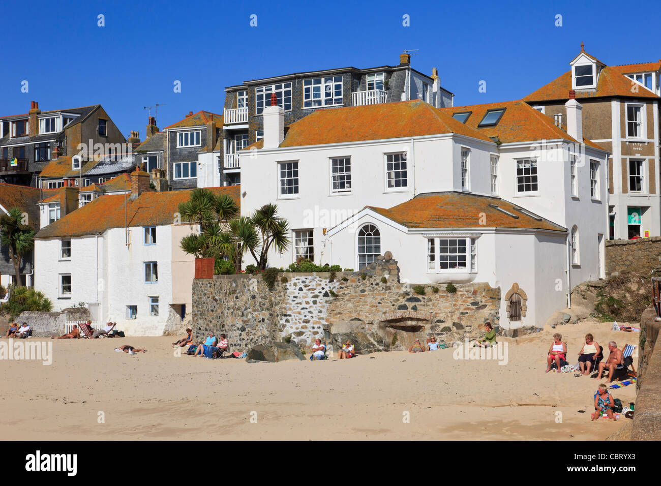 St Ives, Cornwall, England, UK. Traditional white buildings on seafront with people sitting on the sandy beach Stock Photo