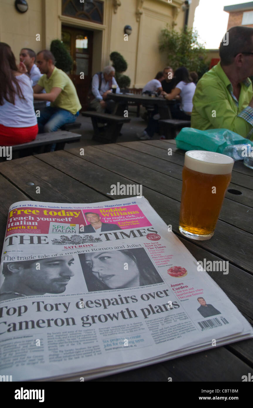 The Times newspaper and pint of bitter beer Earl of Lonsdale pub couryard beer garden Notting Hill district London - Stock Image