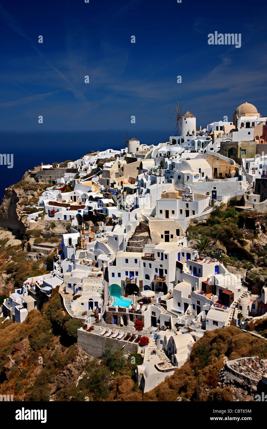 The west part of Oia village, with its famous windmills, hanging over the cliff. Santorini island,  Cyclades, Greece - Stock Image