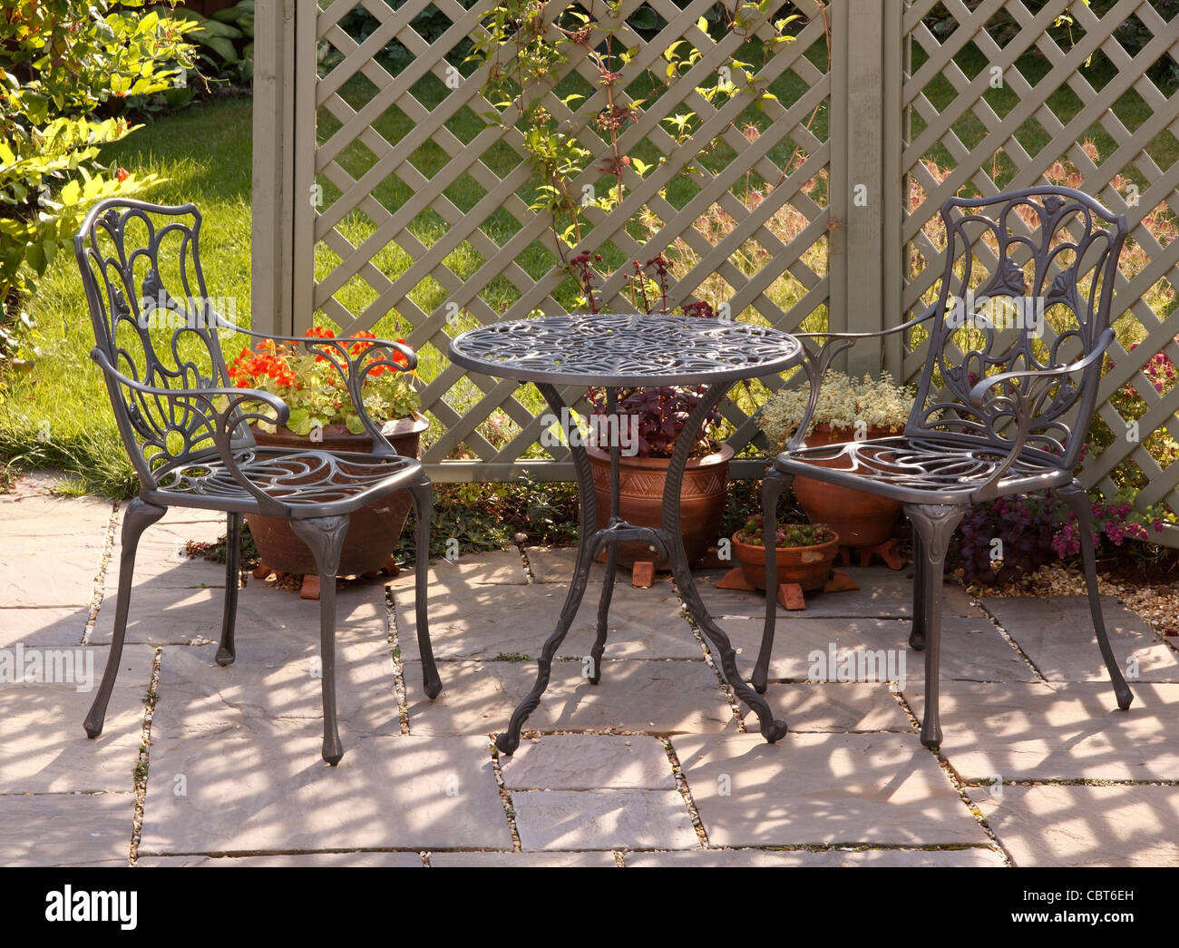 Ornate Grey / Green Painted Aluminium Table And Chairs With Trellis And  Garden Behind, England