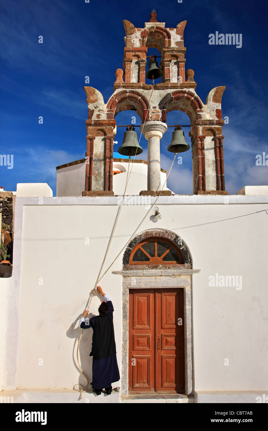 A Greek Orthodox priest ready to toll the bells of a church in picturesque Pyrgos village, Santorini island, Cyclades, - Stock Image