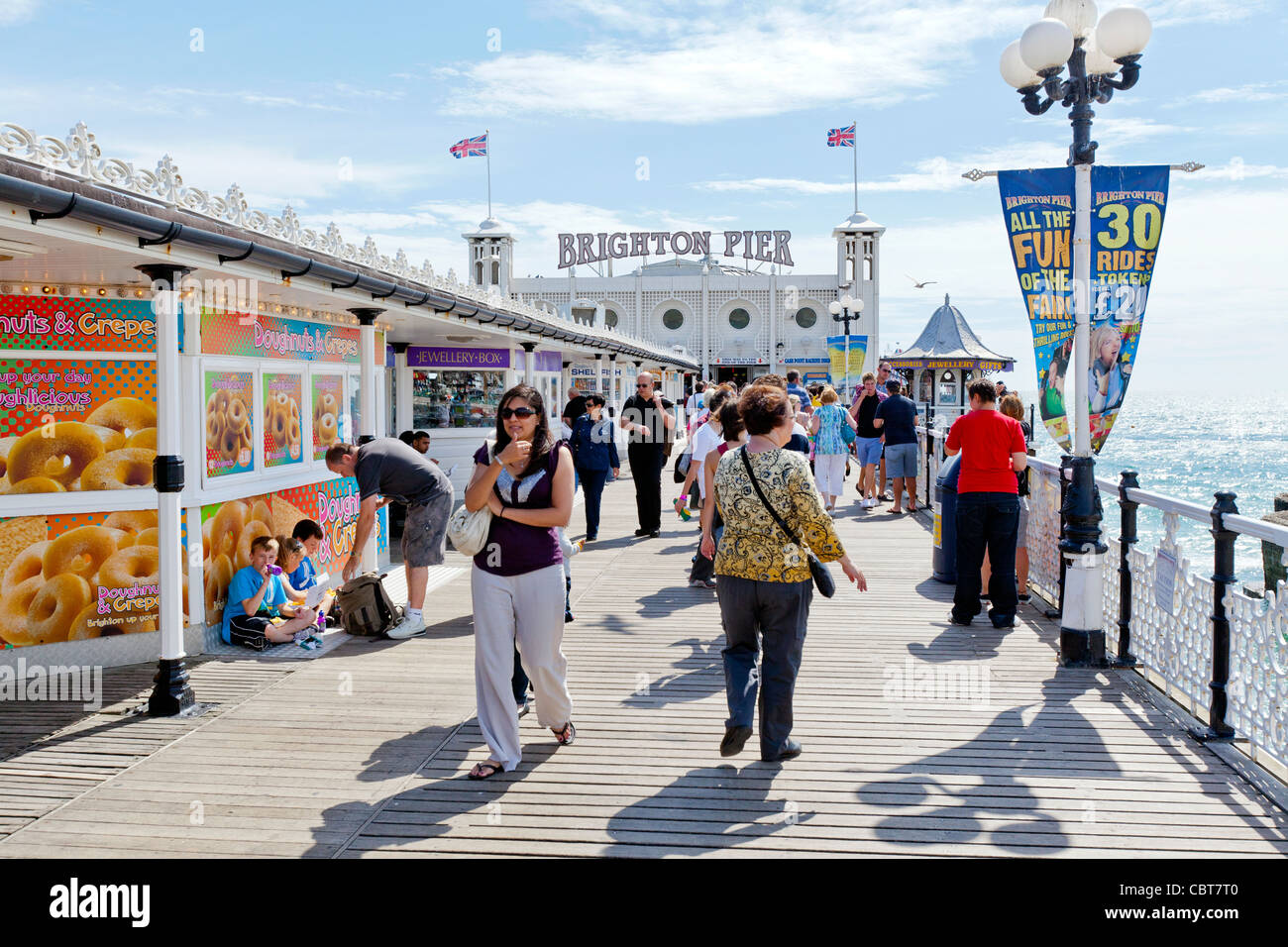 People on holiday and vacation sitting, relaxing, walking and enjoying themselves on the Brighton Pier boardwalk. - Stock Image
