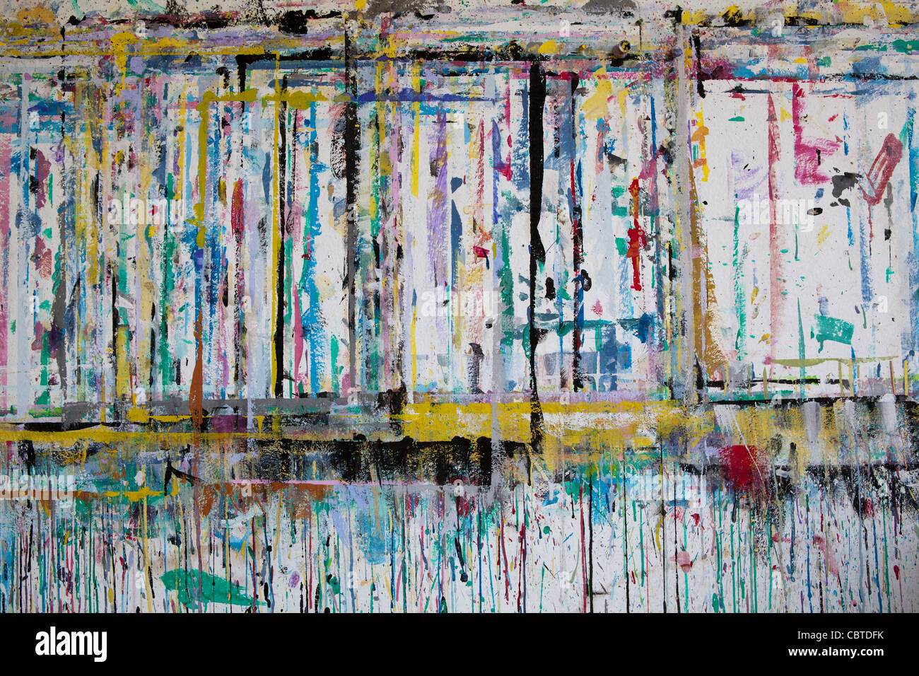 A wall of paper becomes an abstract painting after children remove their artwork from it. - Stock Image