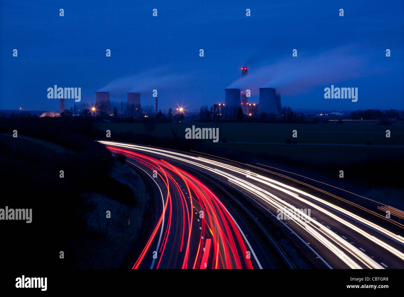 Traffic at night running past a coal fired electricity generating power station, Didcot, oxon, uk - Stock Image