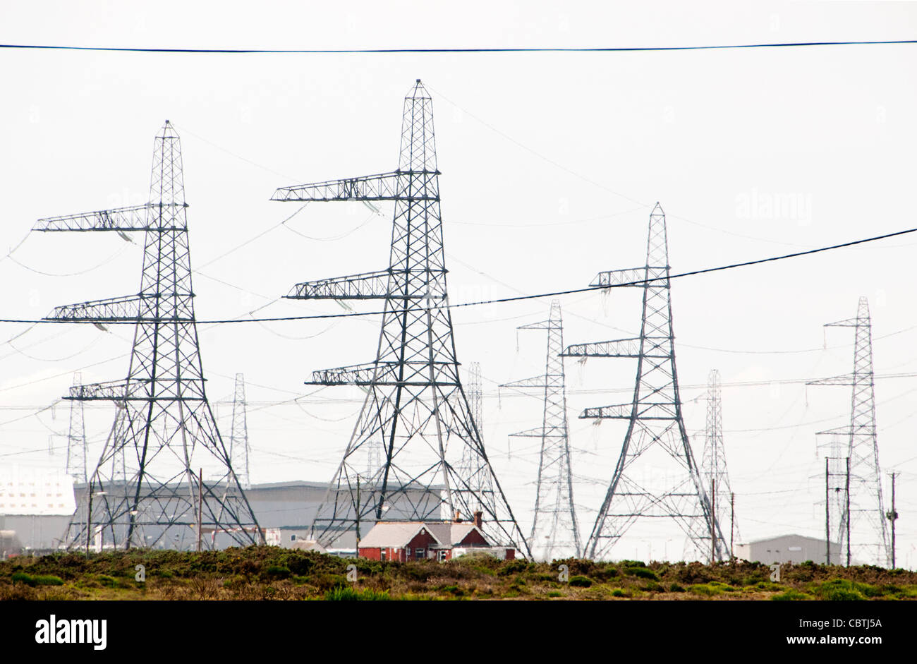Fishermen' small houses contrasting with power lines of the Nuclear Power station, Dungeness, Kent, UK - Stock Image
