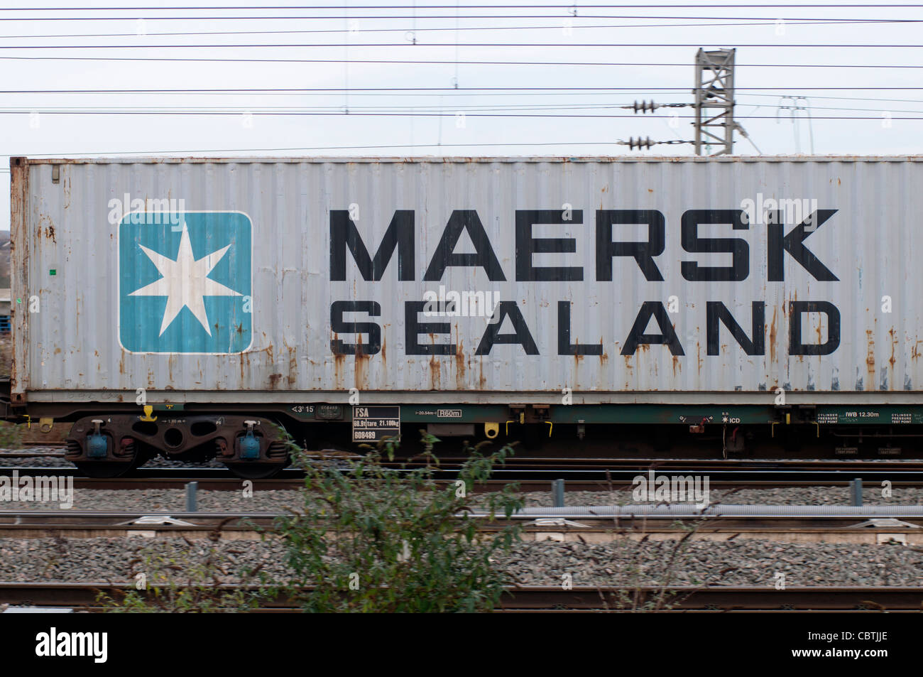Maersk Sealand shipping container passing through Rugby railway station, UK - Stock Image