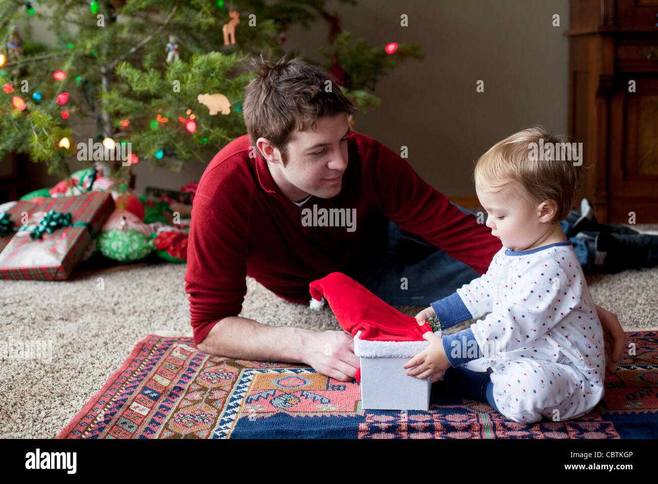 Father watching toddler son open holiday gift  at Christmas. - Stock Image