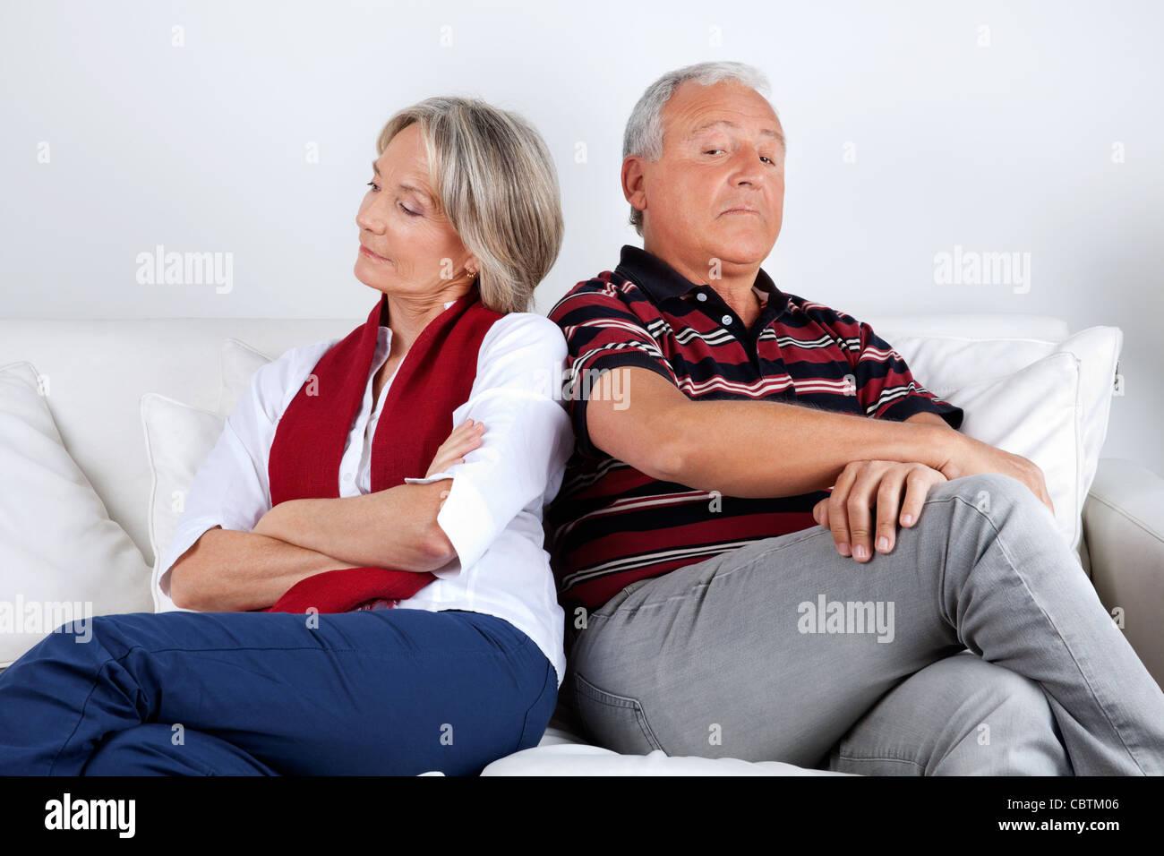 Senior couple sitting on sofa after argument - Stock Image