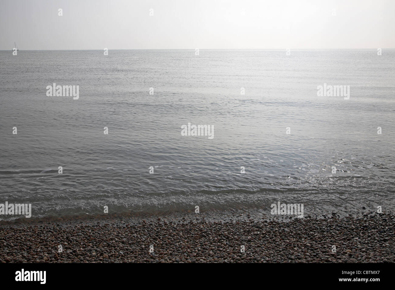 Grey calm water of the North Sea with gentle waves on a still day, from Shingle Street, Suffolk, England - Stock Image
