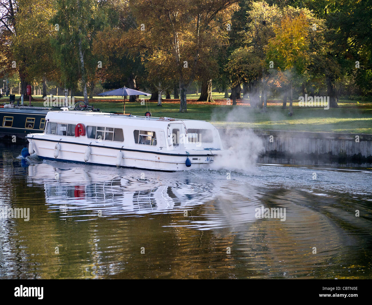 Pleasure boat emitting air pollution- the Thames at Abingdon - Stock Image